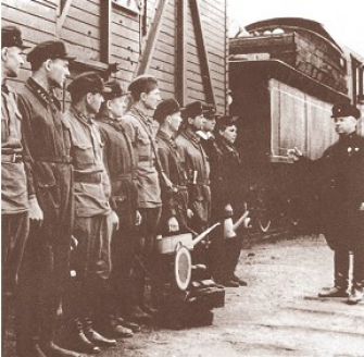 Смотр команды, обслуживающей паровоз. На заднем плане — турной вагон. Москва. 1942 г.